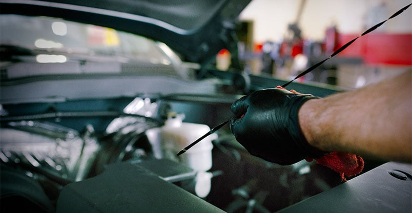 crew member checking oil dipstick